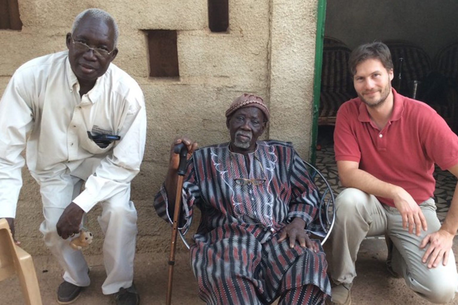 three men in Africa sitting next to cement wall