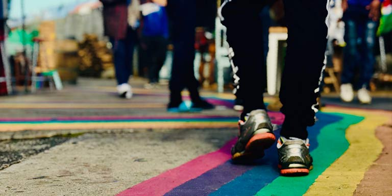 Sneakers walking on rainbow path